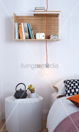A breakfast tray on a white cylindrical bedside table with a pendant lamp with a naked light bulb and a small wall shelf above the bed