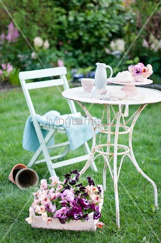 Wooden crate of violas next to vintage garden table and chair