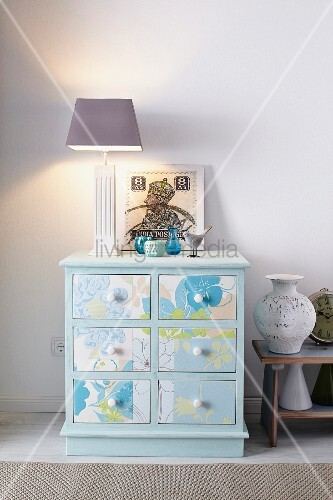 Old chest of drawers rejuvenated with pastel-blue paint and wallpaper