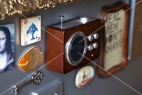 Souvenirs and mementoes (radio, key, tile) mounted on grey wall