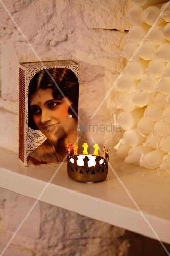 Box of matches with portrait of woman on lid and tealight in brass crown-shaped holder in front of stacked candles