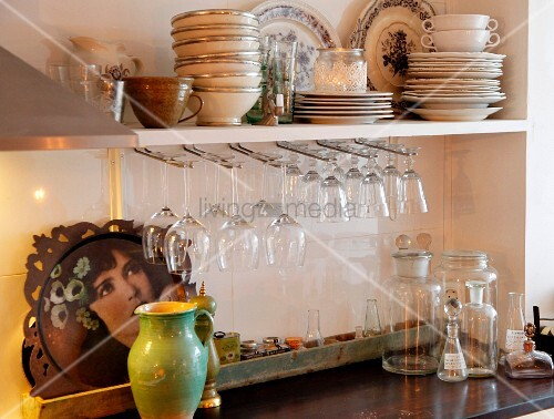 Wine glasses hung from racks below shelves of plates and bowls above kitchen counter