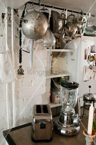 Retro, chrome small kitchen appliances below vintage kitchen utensils hanging from rod