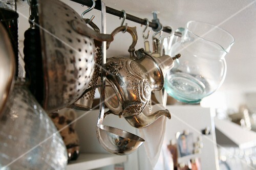 Ornate metal teapot, glass jug and kitchen utensils hanging from rail suspended from ceiling