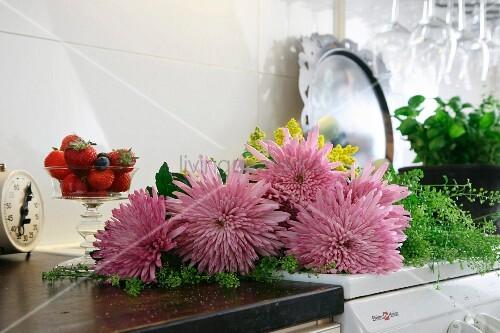 Pink chrysanthemums next to dish of fresh strawberries