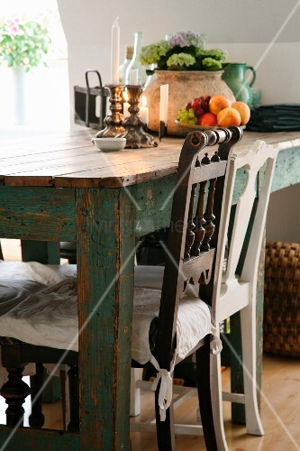 Chairs with carved backrests at rustic table; candlesticks and bowl of fruit on table
