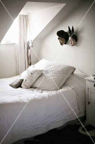 Simple bed with scatter cushions and white bed linen below skylight in sloping ceiling and masks on wall