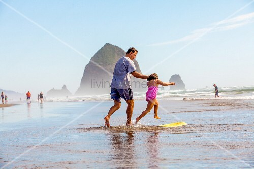Father and daughter with a surf beach in the shallows