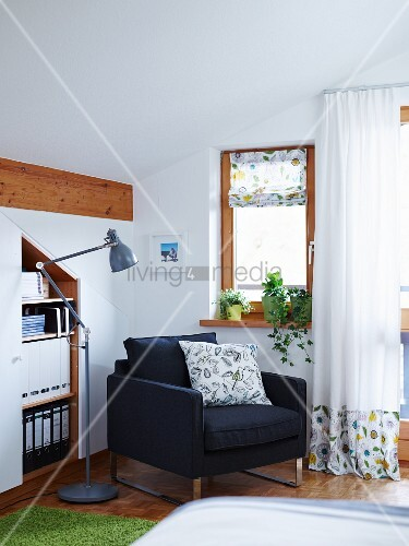 An inviting leather armchair between a built in shelf and a bedroom window with light curtains and a fabric blind