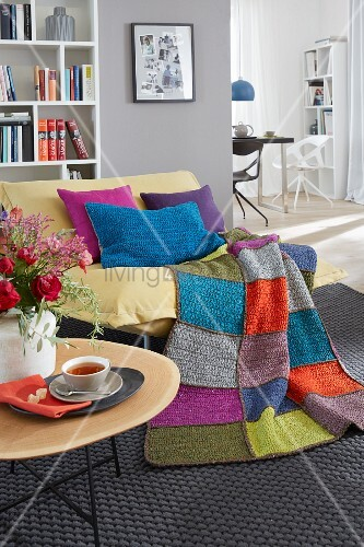 Crocheted cushions and a throw on a yellow armchair