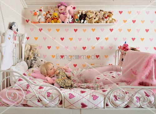 Herzchenmotive Auf Bett Und Wand Im Kinderzimmer; Stofftiersammlung Auf  Holzbord, Darunter Blondes Mädchen Auf Metallbett