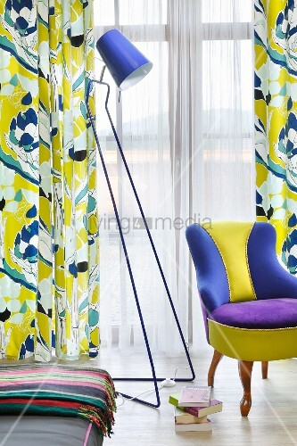 Colourful reading corner with retro standard lamp, multi-coloured easy chair and patterned curtains