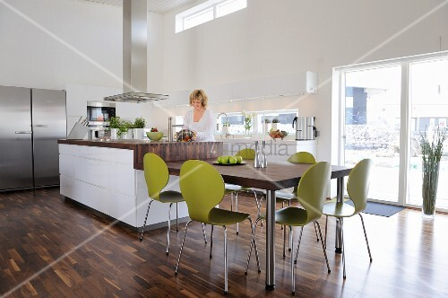 Dining table, green retro chairs and counter in elegant, open-plan kitchen with walnut parquet floor