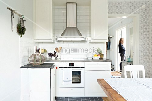 Partially visible dining area in white, country-house kitchen; open door in background with view of woman stood in hall