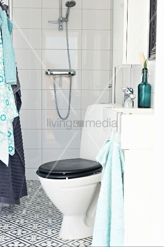Toilet with black lid in modern bathroom with black and white ornamental floor tiles