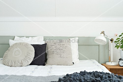 Various scatter cushions in shades of white and grey on bed with grey-painted, wooden headboard