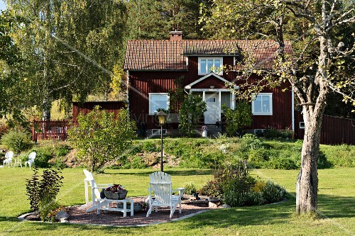 White outdoor chairs on gravel terrace in sunny garden; country house with wooden façade painted Falu red in background