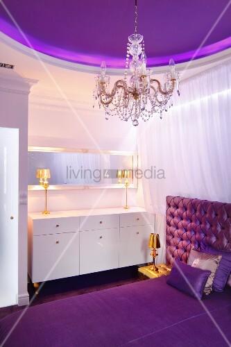 Elegantes Schlafzimmer In Violetttönen Und Goldfarbenen Tischleuchten Auf  Weißer Schminkkommode, Lilafarbene Deckengestaltung Und Kristallkronleuchter