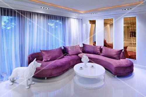lila polstersofa und wei er runder designer couchtisch in offenem wohnraum mit stimmungsvoller. Black Bedroom Furniture Sets. Home Design Ideas