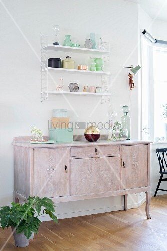 Old bottles and pastel boxes on wall-mounted shelves and vintage cabinet