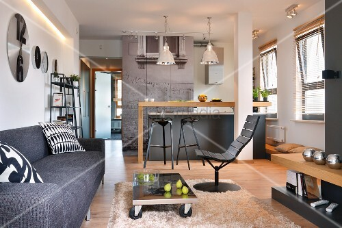 Lounge area with modern, grey couch and low table on castors on flokati rug in front of kitchen area in open-plan interior