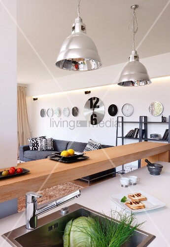 Island counter with integrated sink, minimalist breakfast bar and industrial-style pendant lamps with metal lampshades
