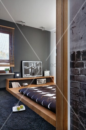 View through open door of designer bed in bedroom with grey wall