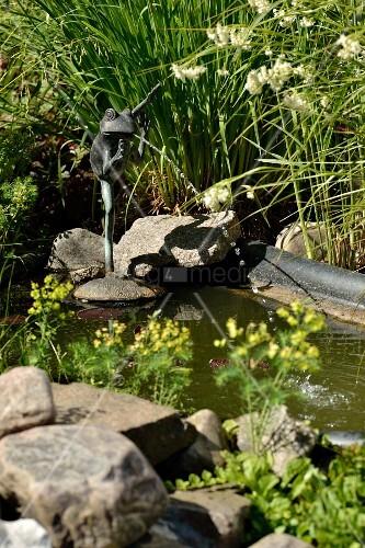 Froschfigur aus Metall als Wasserspeier am Gartenteich