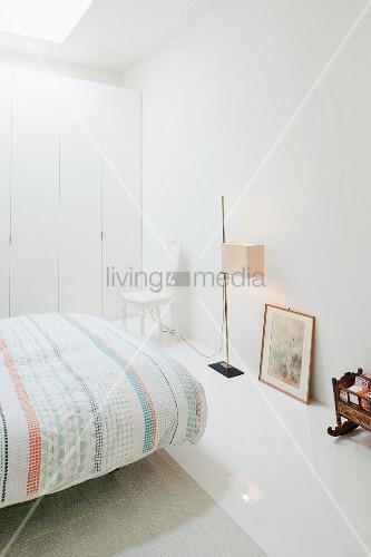 Bett mit gemusterter Tagesdecke, Stehleuchte und Einbauschrank in minimalistischem, weissem Schlafzimmer