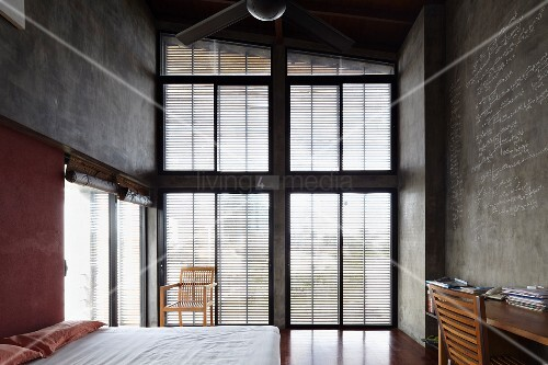Loft-style bedroom with high ceiling and glass wall with louvre blinds