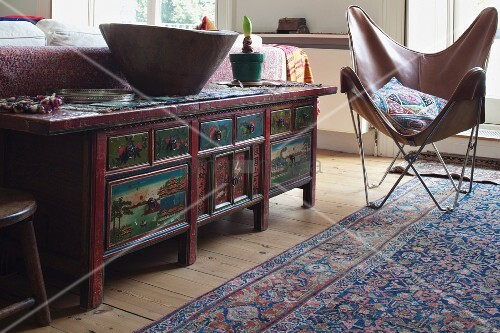 Painted, Mongolian-style cabinet behind sofa, Butterfly easy chair with brown leather cover