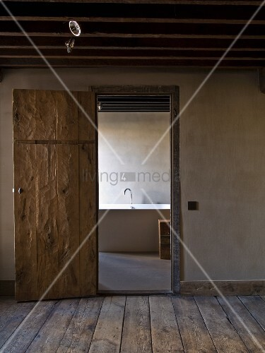 View of bathtub through open, rustic, interior door