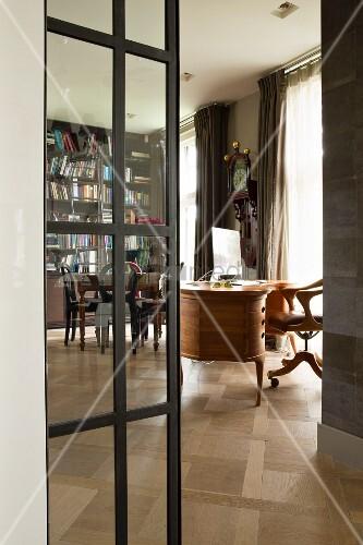 Stahltür mit Glaseinsatz, Blick auf Schreibtisch und Bücherwand