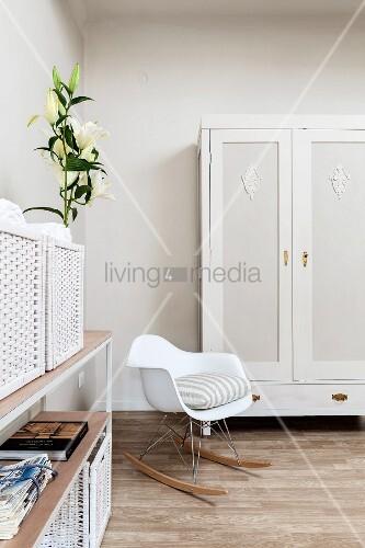 Weißer Designerschaukelstuhl vor lackiertem Kleiderschrank und offenes Regal mit Lilienstrauß und weißen Aufbewahrungskörben in Schlafzimmerecke