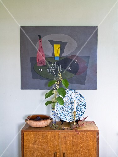 Sprig of leaves in vase and candlestick on wooden cabinet below artwork on wall