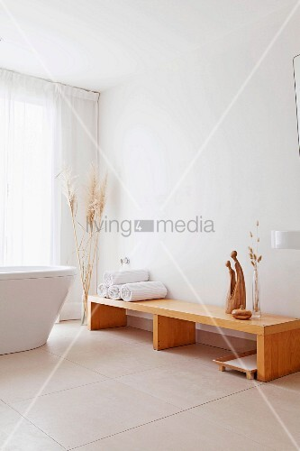 Rolled towels and sculptures on pale wooden bench, free-standing bathtub and large floor tiles in modern bathroom