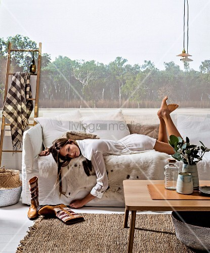Young woman lying on white loose-covered sofa with fur blanket, simple oak coffee table and picture of woodland projected on wall in harmonious interior in natural shades