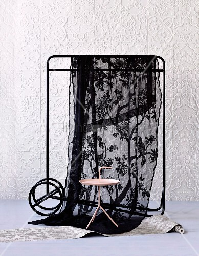 Side table and black voile cloth hanging over clothes rail against white structured wallpaper