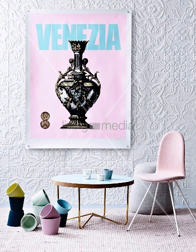 Pastel plant pots, coffee table and retro chairs below vintage poster on structured wallpaper