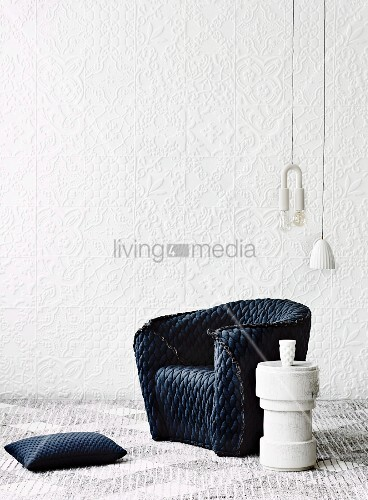 Armchair with quilted, charcoal-grey loose cover, pendant lamps and plinth-style side table against white structured wallpaper
