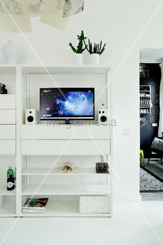 Flachbildschirm über Schubladenmodul in modernem weißem Regal
