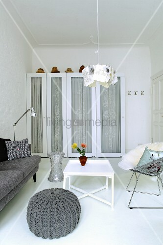 Grey knitted pouffe next to white side table in front of white wardrobe with glass door panels