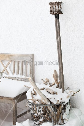 Verschneite Gartenbank und Drahtkorb mit Brennholz vor Hausfassade