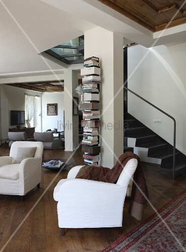 White armchair in open-plan interior with steel staircase