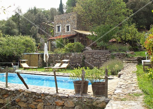 Pool and sun loungers in terraced garden below Mediterranean stone house with terraces and pergola