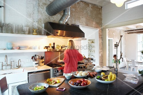 Woman standing at cooker in open-plan kitchen; bowls of fruit on black stone surface of island counter in foreground