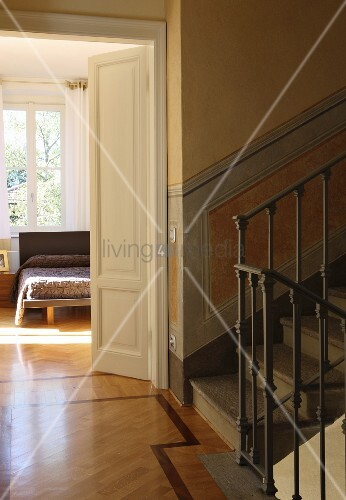 Stairwell in restored villa with view into bedroom through half-open door