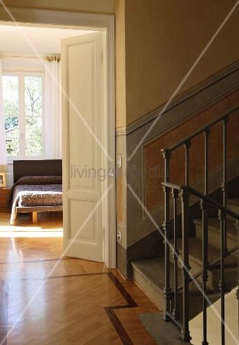 Stairwell in restored villa with view into bedroom through half-open door