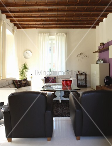 Seating area with white and black leather furniture in living room of renovated villa