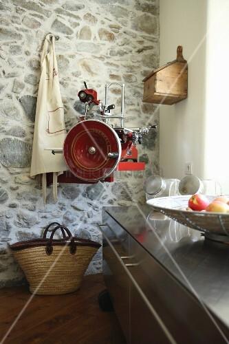 Kitchen base unit on castors, apron and retro slicing machine mounted on stone wall
